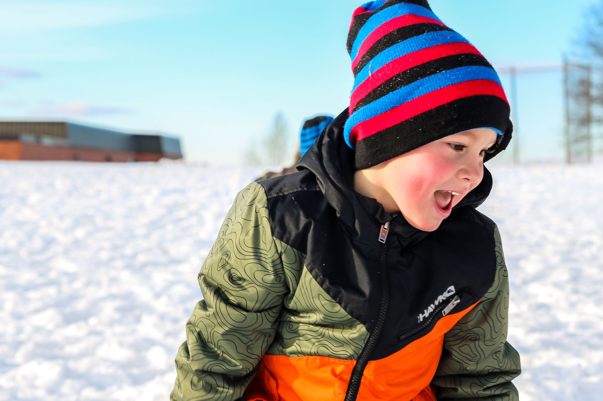 Boy outside in winter, wearing striped hat