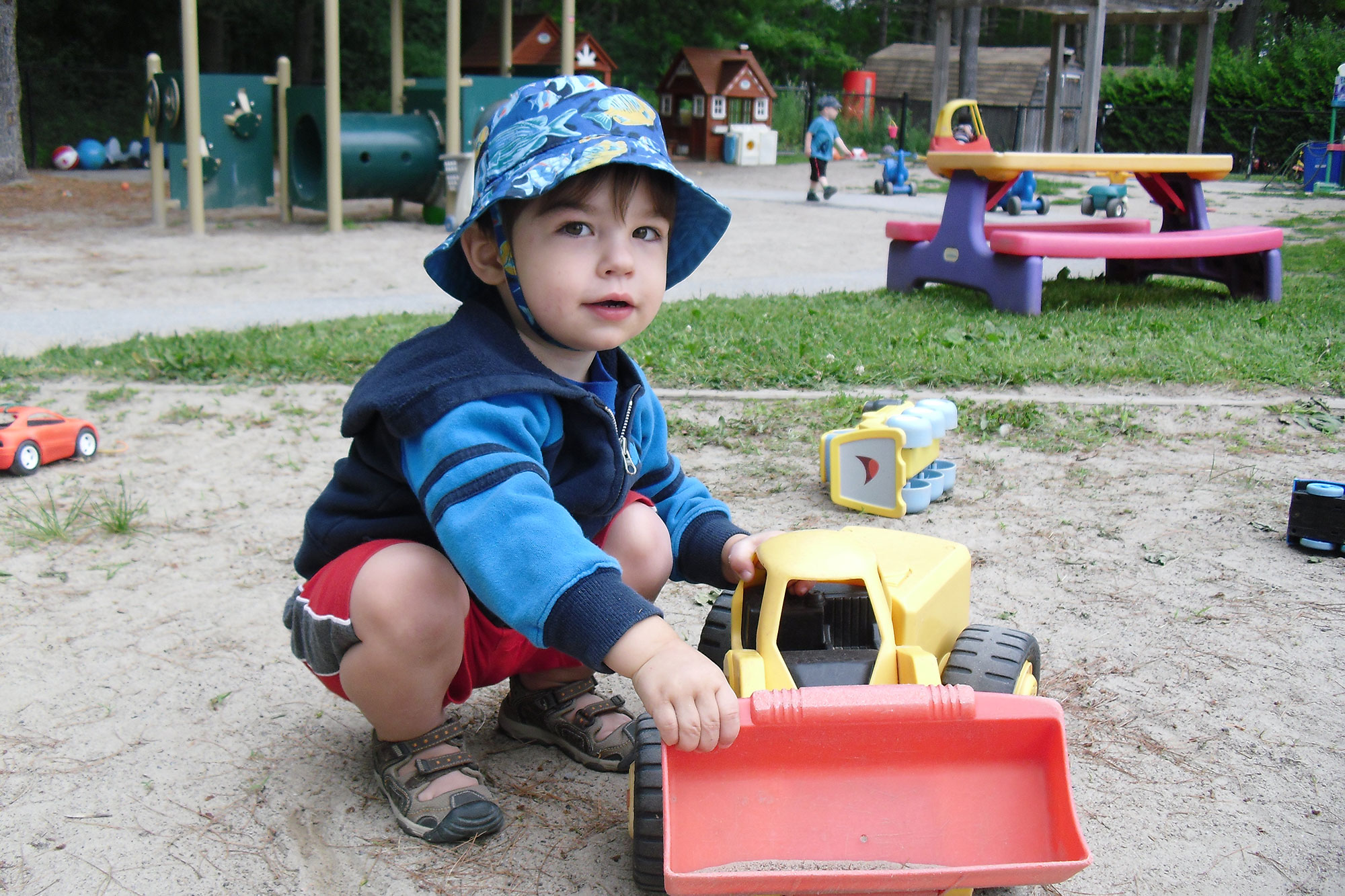 Boy playing with a truck in the sand