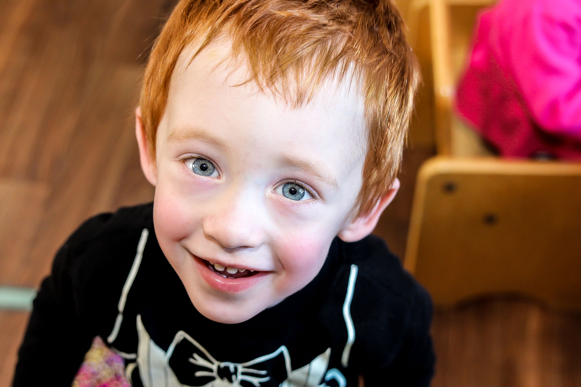 Red-headed little boy smiling at camera