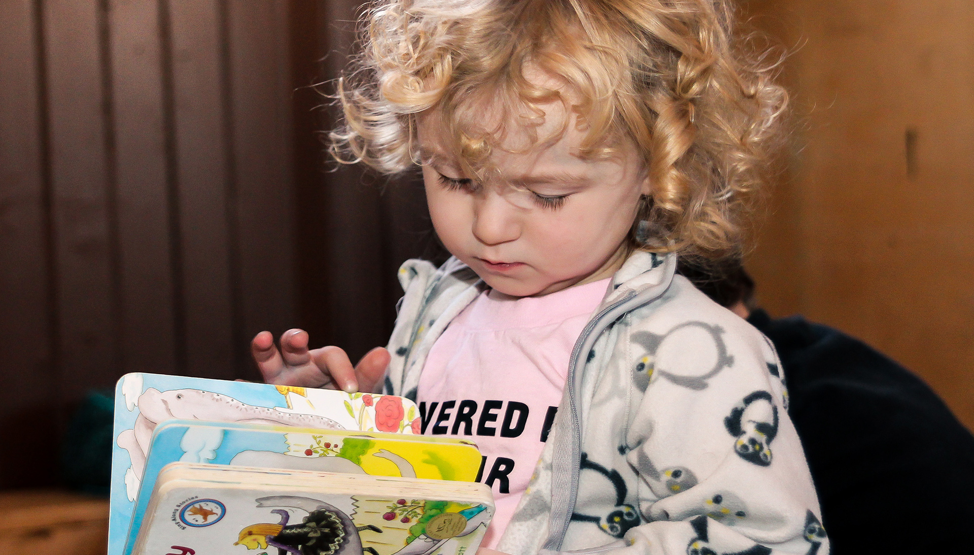 Child with curly blond hair looking at a book