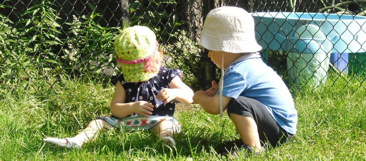 Two children playing outside in grass